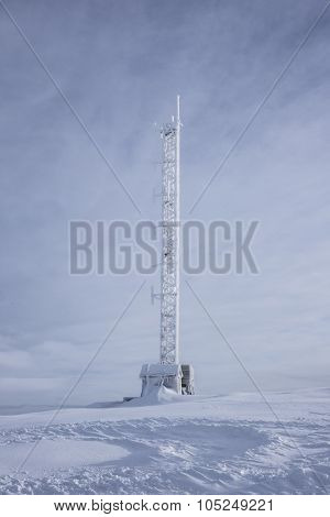 Mobile antennas and TV signal tower covered in snow