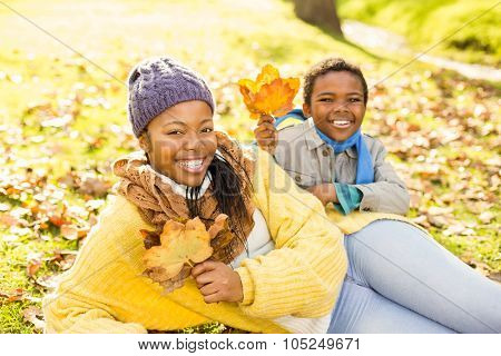 Young mother with her son sitting in leaves on an autumns day