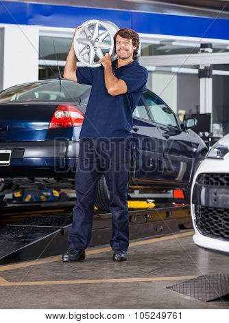 Portrait of happy male technician holding metallic alloy at auto repair shop