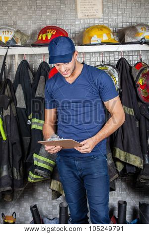 Fireman reading clipboard against uniforms hanging at fire station