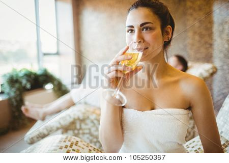 Woman enjoying her glass of champagne at the spa