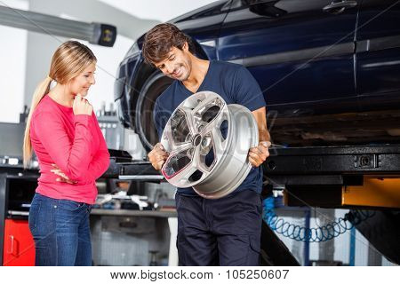 Happy mechanic showing metallic alloy to female customer at garage