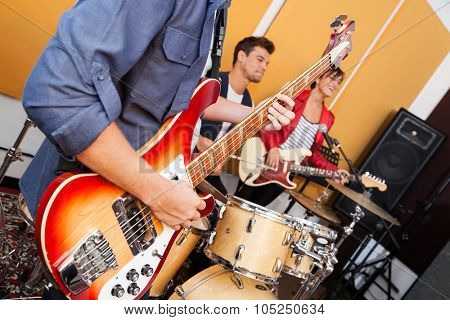 Midsection of male guitarist performing with band in recording studio