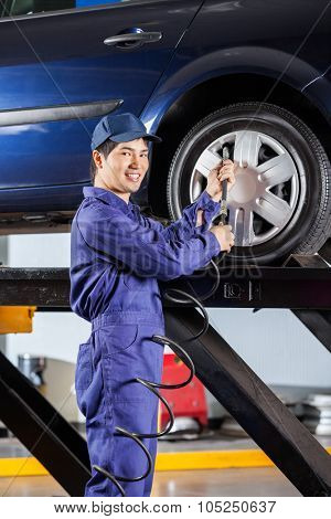 Portrait of smiling male mechanic filling air into car tire at garage