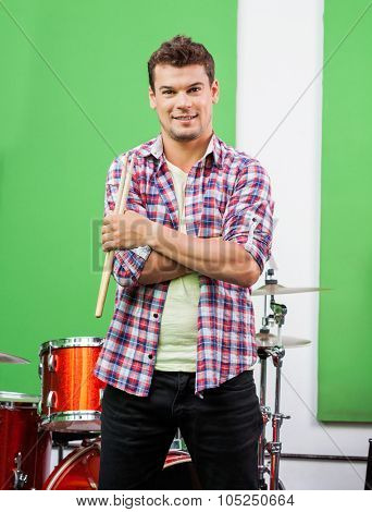 Portrait of confident male drummer holding sticks while standing arms crossed in recording studio