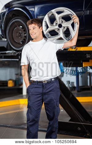 Smiling male mechanic looking away while carrying metallic alloy at auto repair shop