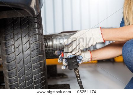 Cropped of female mechanic using pneumatic wrench to fix car tire at repair shop