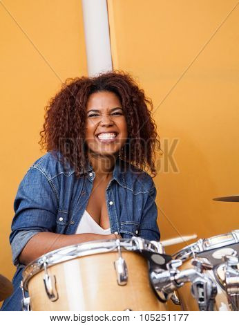 Portrait of energetic female drummer performing in recording studio