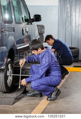 Side view of male mechanics fixing car tires at garage
