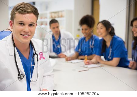 Pink breast cancer awareness ribbon against medical student smiling at the camera during class