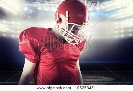 A football player taking his helmet on her head against american football arena