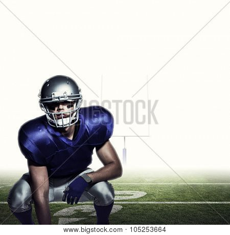 American football player in uniform crouching against american football posts