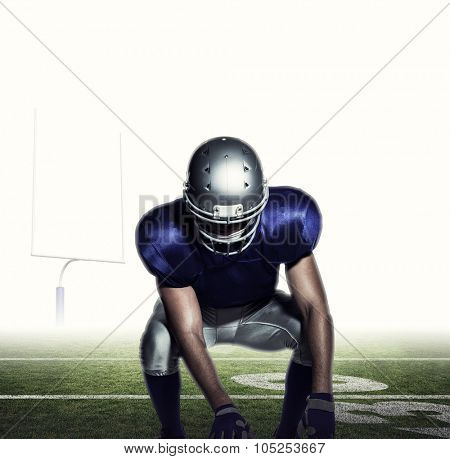 American football player holding ball while crouching against american football posts