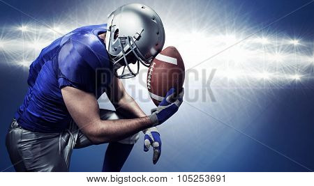 Upset American football player with ball against spotlights