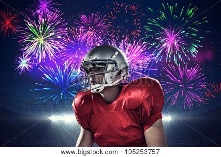 Sportsman holding American football while kneeling against fireworks exploding over football stadium