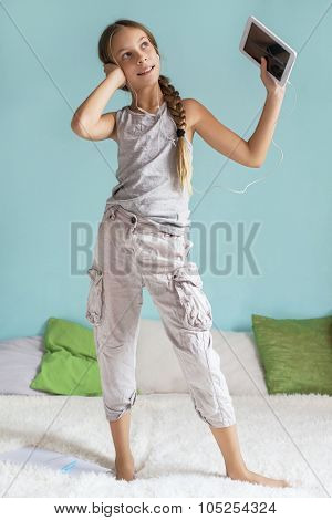 Pre teen girl is dancing in the bed and listening to music with earphones on the tablet at home