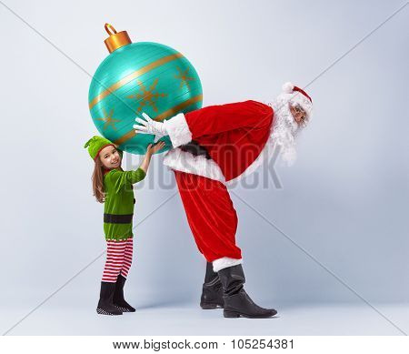 Funny Santa and elf holding together a huge Christmas bauble.