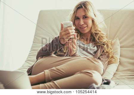 Happy young woman is relaxing on comfortable couch and using mobile phone at home. Photo toned.