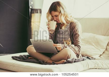 Happy young woman is relaxing on comfortable couch and using laptop at home. Photo toned.