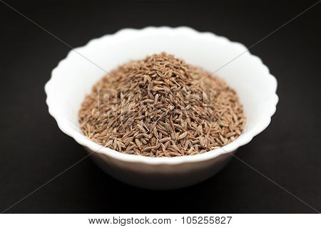 Organic Cumin seed in white bowl.