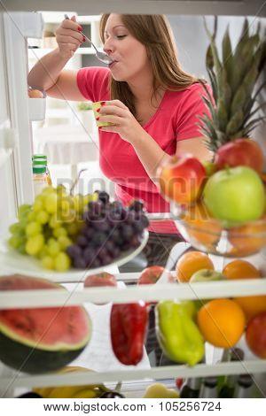 Pretty female sweetens with fresh fruit yogurt from refrigerator