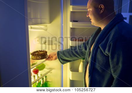 Fat man at night overstep and take whole chocolate cake from refrigerator