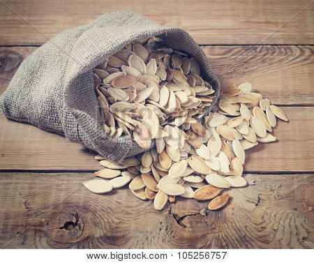 Pumpkin seeds on a wooden background