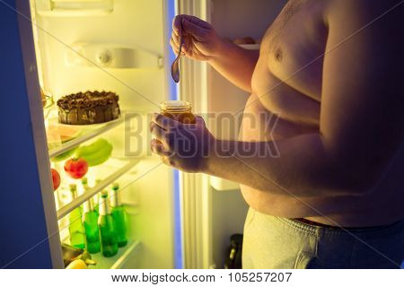 Close up of fat man break diet and takes at night dangerous unhealthy sweet from fridge