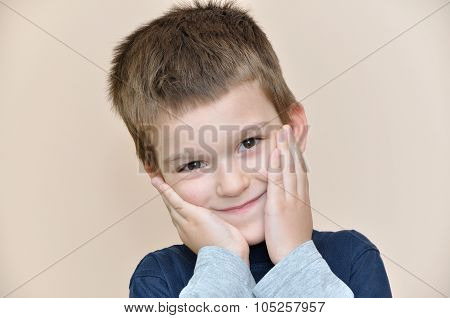Young boy holding hands on the cheeks