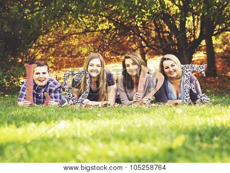 a cute family posing in a park toned with a retro vintage instagram filter effect app or action