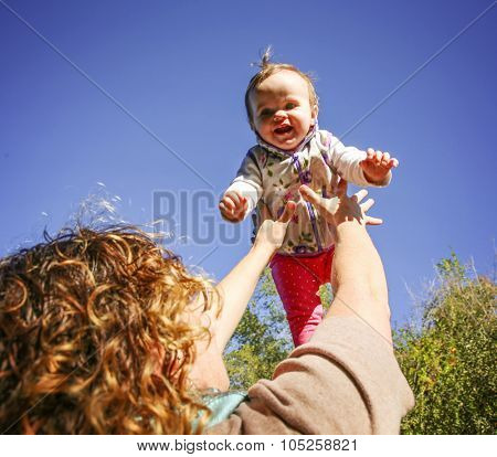 a mother tossing her infant baby into the air