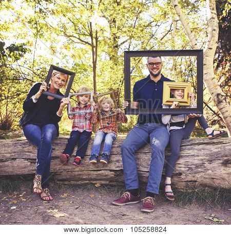a cute family posing with picture frames in a park toned with a retro vintage instagram filter effect app or action
