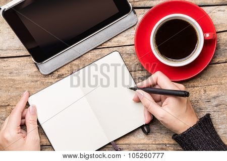 Young Woman Writing Or Drawing Into Notepad
