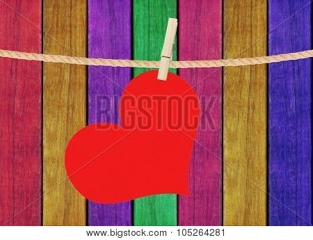 Red Heart Hang On Clothespin Over Painted Wooden Background