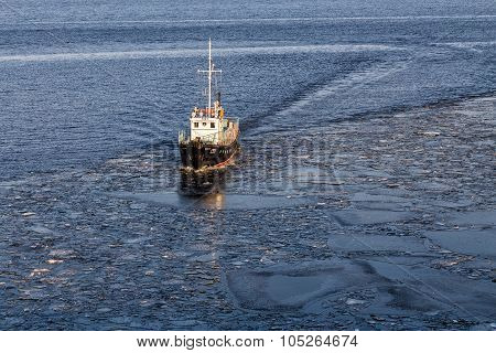 Small Ship Floating In The Water Among The Ice Floes