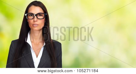 Serious businesswoman wearing glasses over green banner background.