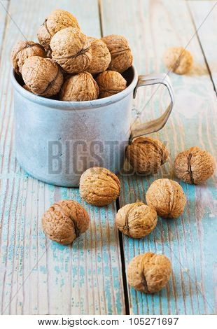Pile of walnuts  a metal mug  on wooden background