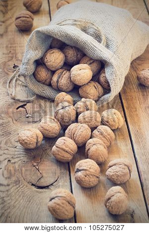 Pile of walnuts in shell inbag on a wooden background toning