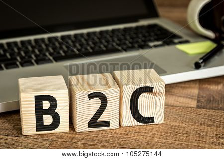 B2C written on a wooden cube in front of a laptop