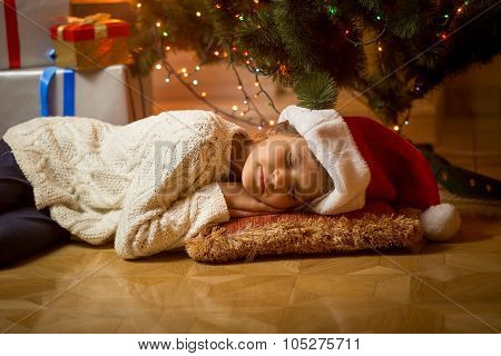 Cute Girl In Santa Hat Fell Asleep Under Christmas Tree
