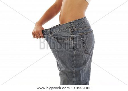 Young woman showing off weight loss with jeans