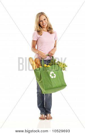 Jovem mulher com mantimentos na bolsa de reciclagem