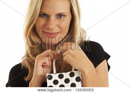 Mulher jovem em preto com pequena sacola de preto e branco