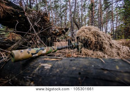 Camouflaged Sniper Lying In Forest And Aiming Through His Scope