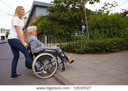 Woman Helping Wheelchair User Over Curbstone