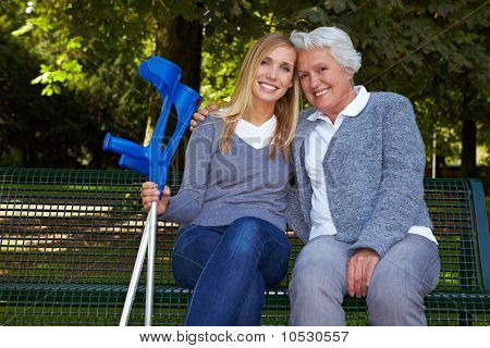 Granddaughter With Handicapped Grandmother On Park Bench
