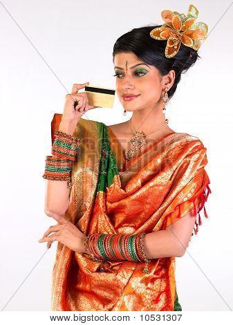 Adolescente en sari, mostrando la tarjeta de crédito