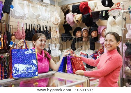 Salesman And Buyer With Purchases At  Counter