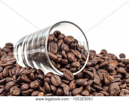 coffee beans pour out from glass shot isolated on white background