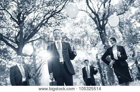 Group of business people holding balloons in the forest
